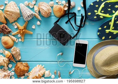 Vacation background on blue wood, top view. Beach accessories, flip flops, photo camera, smartphone and seashells