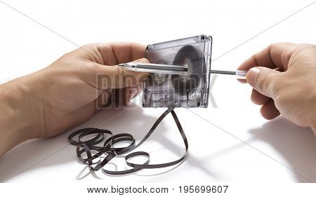 Using pencil to spin mangled cassette tape isolated on white background.