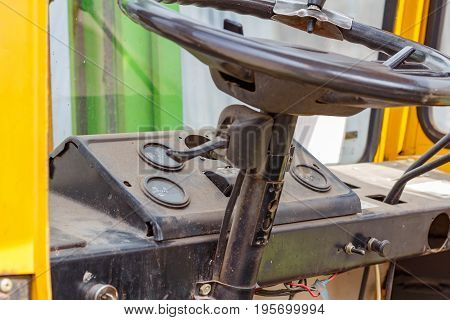 Wheel And Dashboard In The Cab Of The Old Forklift Truck Closeup