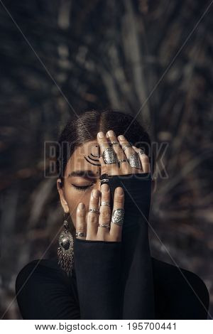 beautiful young woman in black dress cover half of face with hands