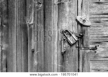 Wooden door surface with handle old padlock old metal and wooden latches. Wooden background and space for text. Black and white texture.