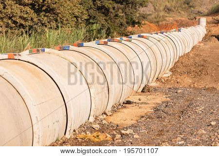 Construction new concrete pipeline for waste water through countryside landscape vegetation.