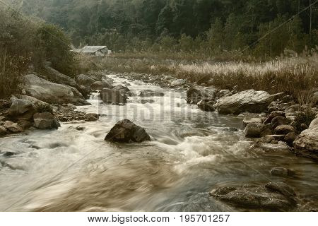 Beautiful Reshi River water flowing through stones and rocks at dawn Sikkim India. Reshi is one of the most famous rivers of Sikkim flowing through the state and serving water to many local people. Tinted image.
