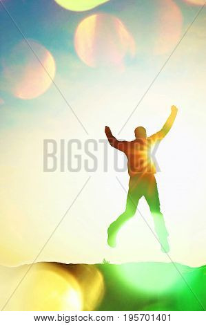 Film Grain. Jumping Man. Young Crazy  Man Is Jumping On Colorful Sky Background.silhouette Of Jumpin