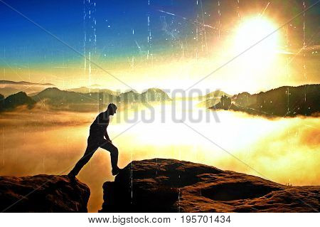 Film Grain. Hiker In Black Is Jumping Between The Rocky Peaks. Wonderful Daybreak In Rocky Mountains
