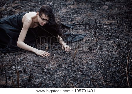 Sad girl sitting on the burned-out land. Concept of environmental disaster. Global problems with ecology. Young attractive multi-racial Asian Caucasian woman in black dress on nature