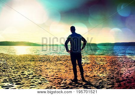 Film Grain. Silhouette Of Person In Sportswear And Short Hair On Beach Seeing Into Morning Sun Above