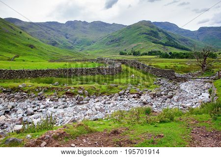 Views in Lake District National Park, England, stone walls, stream, mountains on the background, selective focus