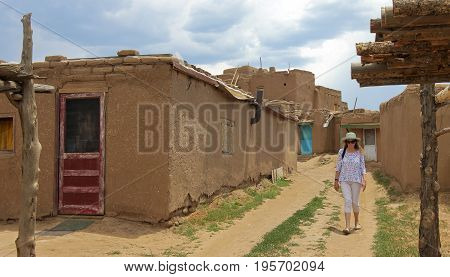 TAOS, NEW MEXICO, JULY 5. The Taos Pueblo on July 5, 2017, near Taos, New Mexico. A Woman Tourist Walks a Street in the Taos Pueblo near Taos in New Mexico.