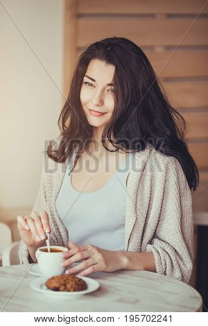 Cafe city lifestyle woman drinking and eating sitting intdoors in trendy urban cafe. Romantic young modern mixed race Asian Caucasian female model in fashion retro look style looking away