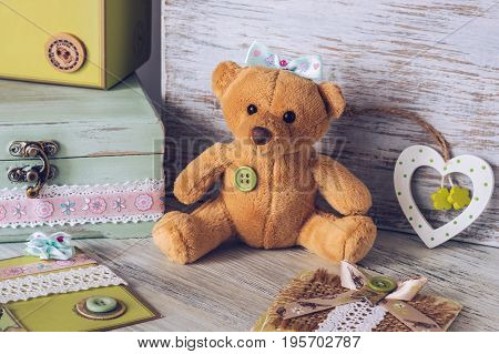 Soft toy bear girl with a bow. Toy on a wooden table with a box and a heart.