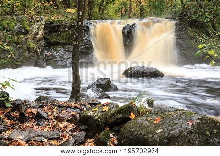 Root Beer Falls in Wakefield Michigan in the Upper Peninsula of Michigan. Tannin colored water flows over rock and spills into Planter Creek