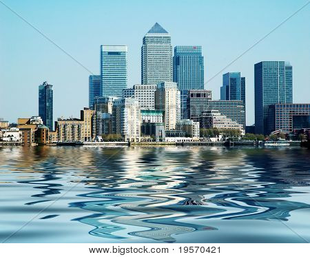 Buildings at Canary Wharf London reflected in the river Thames on a beautiful clear day