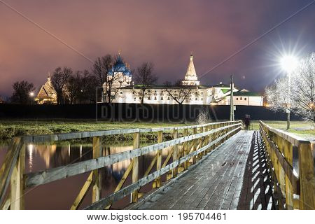 Suzdal, Russia. Nativity Cathedral, the bell tower and Archbishop's chambers of Suzdal Kremlin at night in summer and wooden bridge