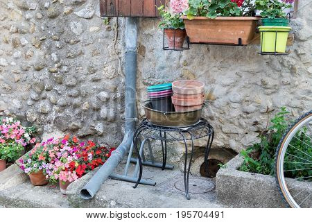 Part of typical provence house with drain pipe flowers and bicycle