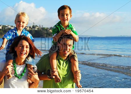 Beautiful young family playing at the beach in the morning sun...