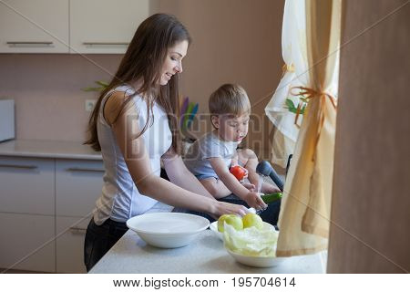 kitchen little son helps mom wash fruits and vegetables in the sink