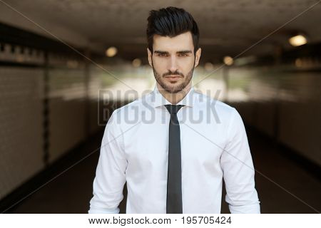 Handsome man standing in underpass, looking at camera.