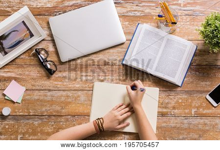 business, education and people concept - hands with book writing to notebook at wooden table