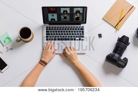photography, people and technology concept - hands of photographer with camera reviewing model photoshoot on laptop computer screen at table