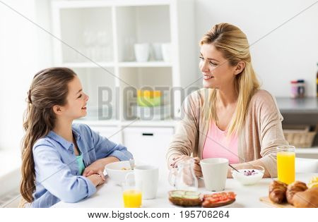 healthy eating, family and people concept - happy mother and daughter having breakfast at home kitchen