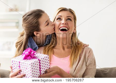 people, holidays and family concept - happy girl giving birthday present to mother at home