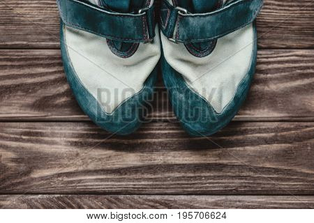 Sporty climbing shoes on a wooden background.
