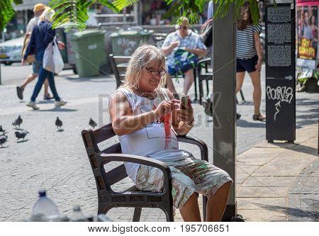 Senior Long Hair Man Looking In His Mobile Phone