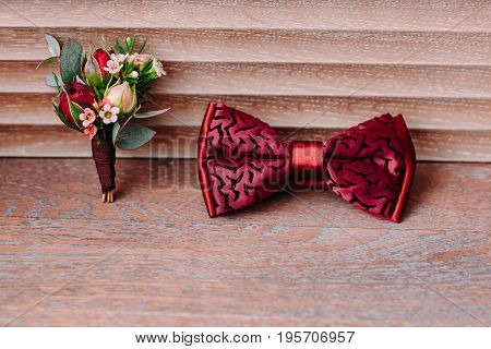 Stylish and boutonniere red bow tie with an ornament on wooden background, groom getting ready in morning before the wedding. Top view