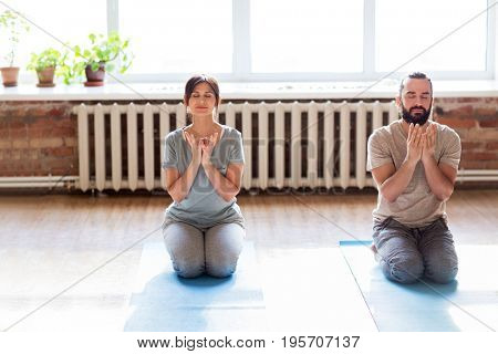 fitness, people and healthy lifestyle concept - man and woman doing lotus seal gesture and meditating in seated pose at yoga studio