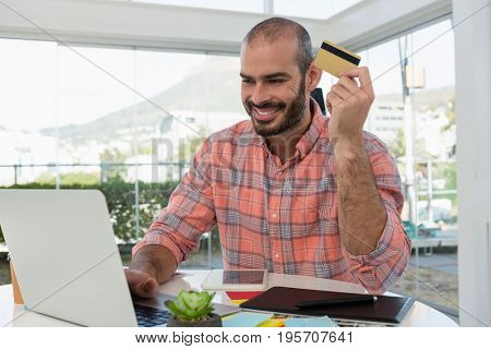 Smiling graphic designer holding credit card while using laptop at desk in studio