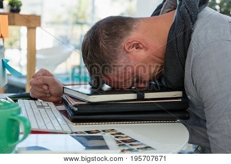 Frustrated man sleeping on files at desk in office