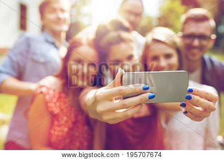 technology, people and friendship concept - happy friends with smartphone taking selfie at summer party