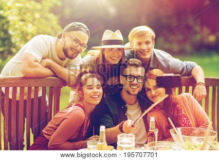 leisure, party, technology, people and holidays concept - happy friends taking picture with smartphone selfie stick and gathering for dinner at summer garden party