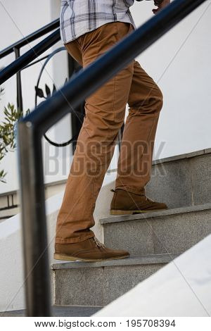 Low section of young man moving up on staircase