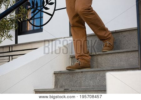 Low section of man moving down on steps