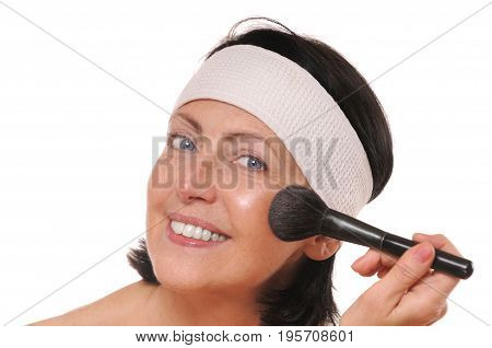 Mature woman applying makeup. Beauty and care concept