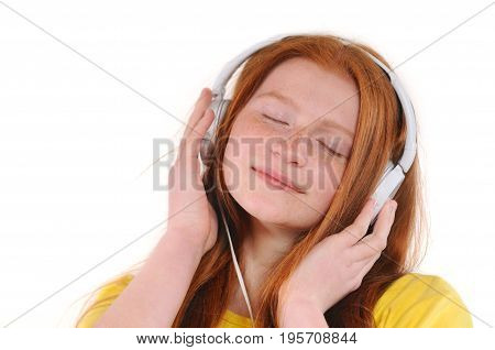 Beautiful young woman with headphones relaxing by listening music. Chill out and leisure concept. Natural redhaired teenage girl. Isolated on white background