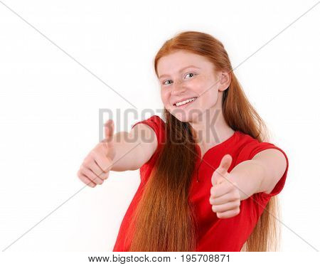 Red hair teenager girl in a red shirt showing a thumbs-up on white background. Happy smiling lifestyle people concept. Human emotions. Natural redhaired teenage girl.