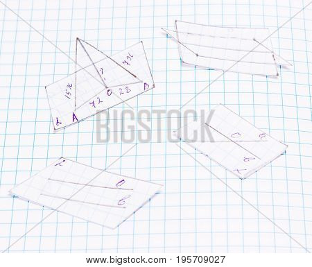 Cut out geometric figures on a sheet of notebooks drawn by pencil by hand education is very important