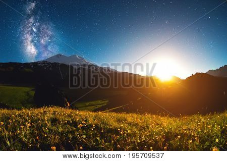 A beautiful night landscape of the Caucasus volcano Elbrus at sunset on the background of the Milky Way and stars in the flowering season of buttercups.
