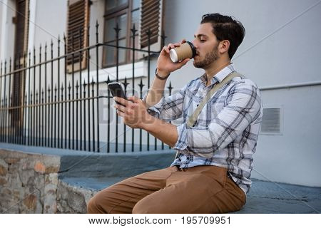 Man having drink while using mobile phone on retaining wall