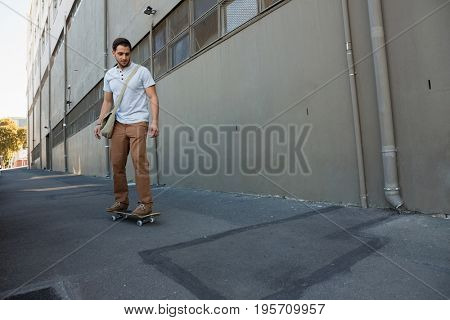 Full length of young man skating on footpath by building