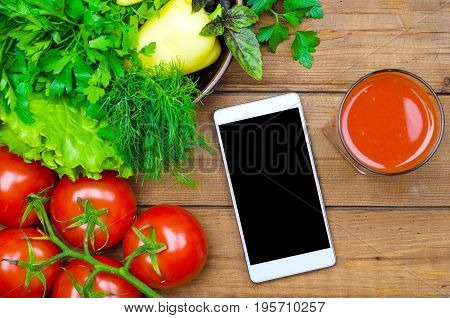 Fresh Tomato Juice, Tomatoes And Smartphone On A Wooden Table Top View, Copy Space.