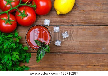 Tomato Juice, Tomatoes And Greens On A Wooden Table, Top View, Free Space.