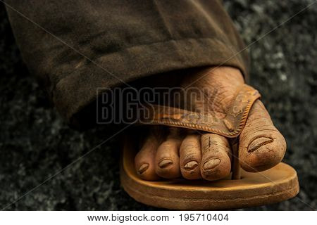 Travelling on a shoestring. Wrinkled foot of jungle guide in flip flops close up. Travelling background. Laos Asia.