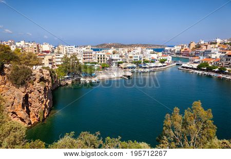 Aerial view of Agios Nikolaos, a coastal picturesque town in Eastern Crete Greece, with Lake Voulismeni with marina, waterfront cafes and buildings