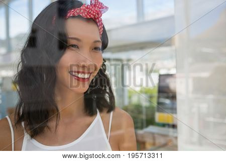 Smiling thoughtful businesswoman looking through at office window seen through glass