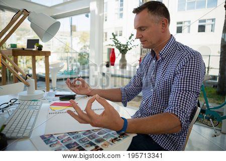 Designer meditating while sitting at desk in office