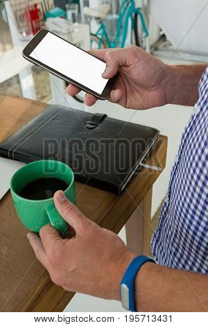 Midsection of designer using mobile phone while holding drink at table